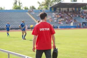 20909691 - sports doctor, during the match, the players treat injuries